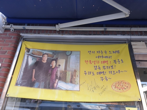 This placard on display at a pizzeria in southern Seoul shows Bong Joon-ho posing with the pizzeria's owner. (Yonhap)