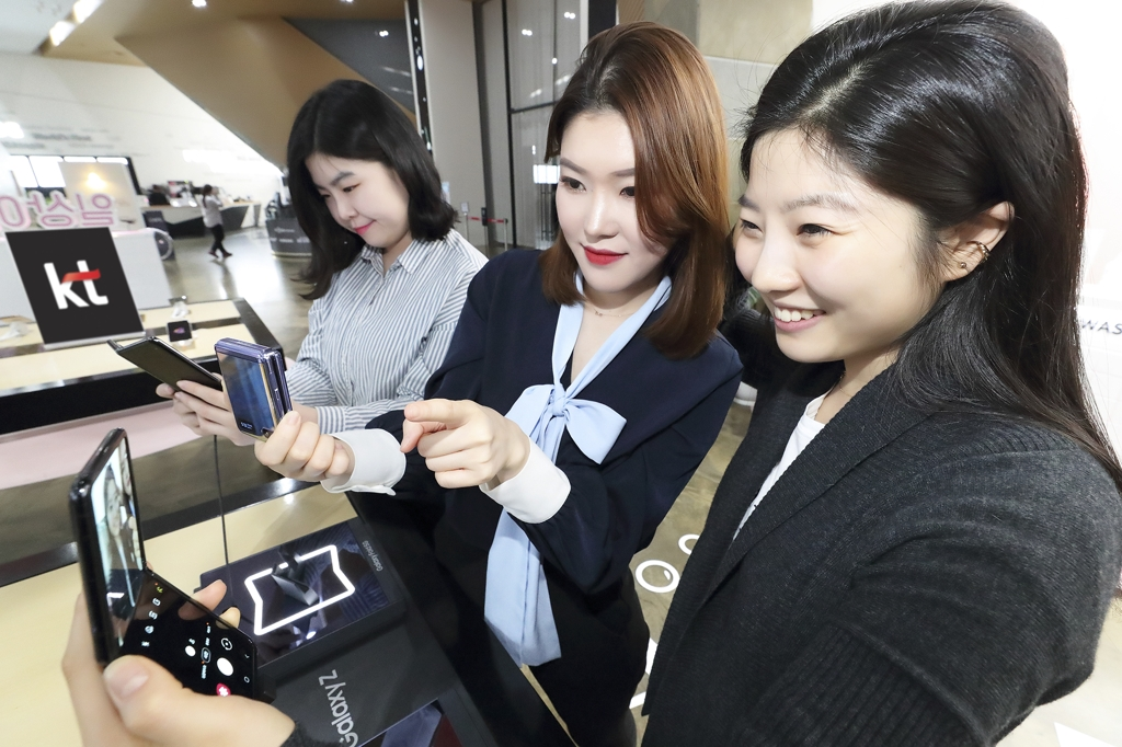 This photo provided by KT Corp. on Feb. 14, 2020, shows people checking Samsung Electronics Co.'s latest foldable phone, the Galaxy Z Flip, at a KT store in Seoul. (PHOTO NOT FOR SALE) (Yonhap)