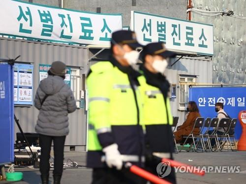 Police officers wearing masks stand guard at a medical center in Daegu, a city 300 kilometers southeast of Seoul, on Feb. 20, 2020, as people suspected of having been infected with the new coronavirus arrive to receive tests. (Yonhap)