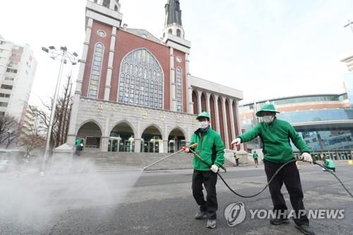 Workers disinfect an area around Myungsung Church, a Presbyterian church with 80,000 followers, in Seoul on Feb. 26, 2020, after a pastor of the church tested positive for the new coronavirus. (Yonhap)