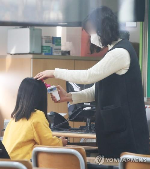A pupil has her body temperature taken by a teacher during a day care program at an elementary school in Suwon, just south of Seoul, on March 2, 2020. (Yonhap)