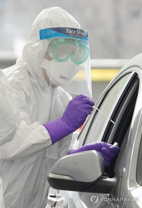 A medical worker collects a sample from a citizen in a car at a drive-through clinic in front of Seoul Olympic Main Stadium on March 3, 2020, to test for the new coronavirus. (Yonhap)