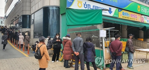 People wait in line to buy masks in front of a local supermarket in the southeastern city of Daegu on March 7, 2020. (Yonhap)