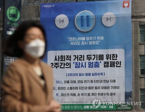 This undated file photo shows a citizen walking past a social-distancing campaign poster in Seoul. (Yonhap)