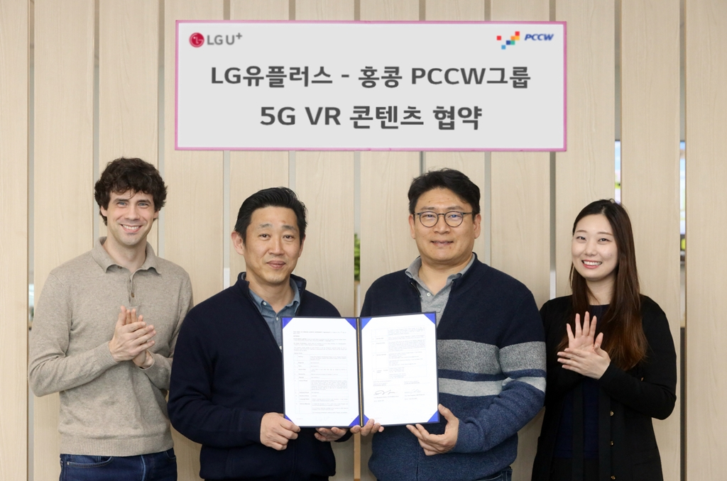 In this photo provided by LG Uplus Corp. on March 22, 2020, LG Uplus officials pose for a photo at the company's office building in Seoul after signing an agreement with PCCW Group, which runs Hong Kong's top telecommunication firm, on supplying 5G VR content. (PHOTO NOT FOR SALE) (Yonhap)