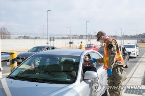 A military guard at U.S. Army Garrison Humphreys in Pyeongtaek, 70 kilometers south of Seoul, checks the temperature of a driver to screen entrants to the compound for the novel coronavirus on Feb. 28, 2020, in the photo provided by United States Forces Korea. (PHOTO NOT FOR SALE) (Yonhap)