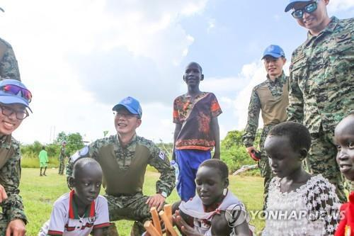 "Members of South Korea's Hanbit Unit play the Korean traditional folk game ""yut"" with children in South Sudan on Sept. 12, 2019, in this photo provided by the Joint Chiefs of Staff. (PHOTO NOT FOR SALE) (Yonhap)"