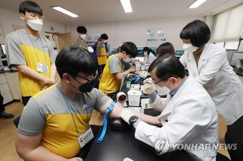 This file photo taken Feb. 3, 2020, shows aspiring soldiers wearing masks having their blood taken during a medical checkup at the Seoul office of the Military Manpower Administration as part of the year's first batch of applicants evaluated by the office. All able-bodied South Korean males are required to serve roughly two years in the military. (Yonhap)