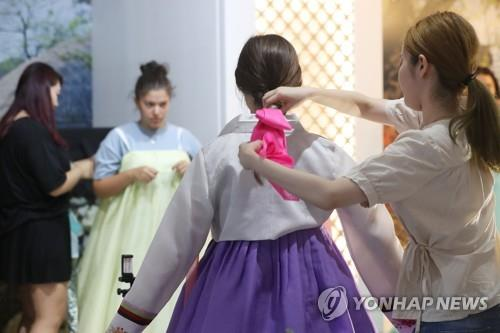 Tourists try on the traditional Korean dress hanbok during a trip in South Korea. (Yonhap)
