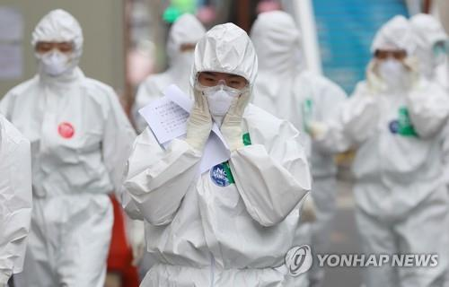 Medical workers examine their masks and other personal protective equipment before entering a hospital ward for coronavirus patients in Daegu, southeastern South Korea, on April 13, 2020. (Yonhap)