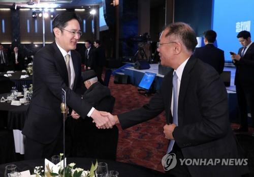 Samsung Group Vice Chairman Lee Jae-yong (L) shakes hands with Hyundai Motor Group Executive Vice Chairman Chung Euisun at a New Year's meeting in Seoul on Jan. 2, 2020. (Yonhap)
