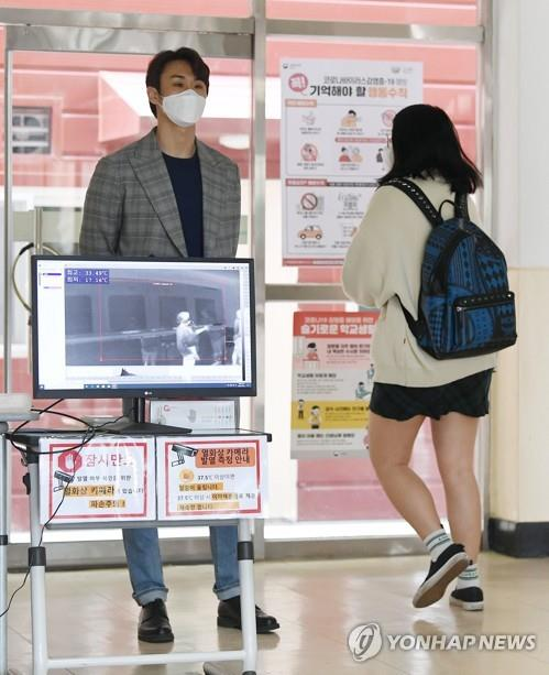 A student passes by a thermal imaging camera set up at a school in Seoul on May 20, 2020. (Yonhap)