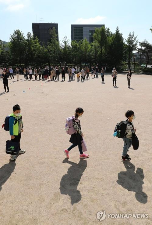 Students maintain distance from one another after arriving at Cheongun Elementary School in Seoul on May 27, 2020, amid the coronavirus pandemic.