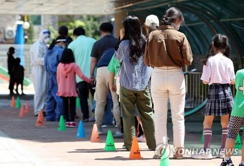 Students and parents wait in line to take COVID-19 tests at a temporary outdoor clinic at an elementary school in Incheon, west of Seoul, on May 29, 2020, as new infections broke out in the city. (Yonhap)