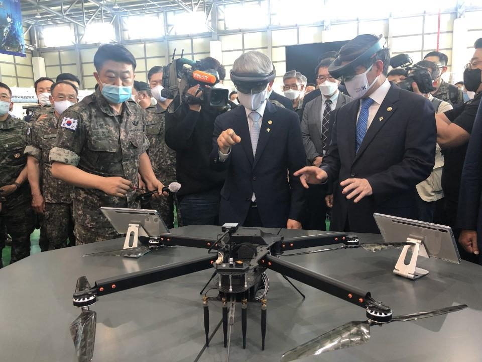 Defense Minister Jeong Kyeong-doo (R) and Science Minister Choi Ki-young (C) experience an augmented reality (AR) command and control platform during their visit to the 20th Fighter Wing in Seosan, South Chungcheong Province, on June 9, 2020, in this photo provided by the defense ministry. (PHOTO NOT FOR SALE) (Yonhap)