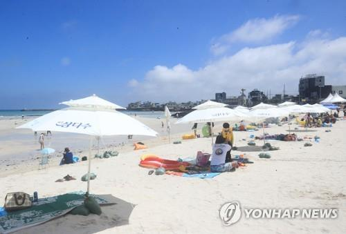 Vacationers keep a distance from one another at Hyeopjae Beach of Jeju Island on its opening day, July 1, 2020. (Yonhap)