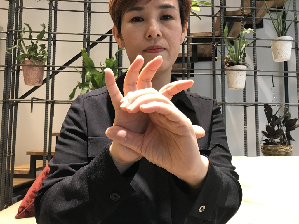 "Sign language interpreter Koh Koung-hee signs the term ""COVID-19"" during a recent interview with Yonhap News Agency in Seoul. Koh, who showed up in an olive-colored shirt, changed to black attire to better demonstrate her signing. (Yonhap)"