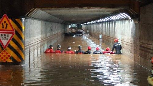 This photo, provided by the Busan Metropolitan Police Agency, shows firefighters searching an underpass submerged in rain water on July 24, 2020, after three people were found dead in their cars there the previous day. (PHOTO NOT FOR SALE) (Yonhap)
