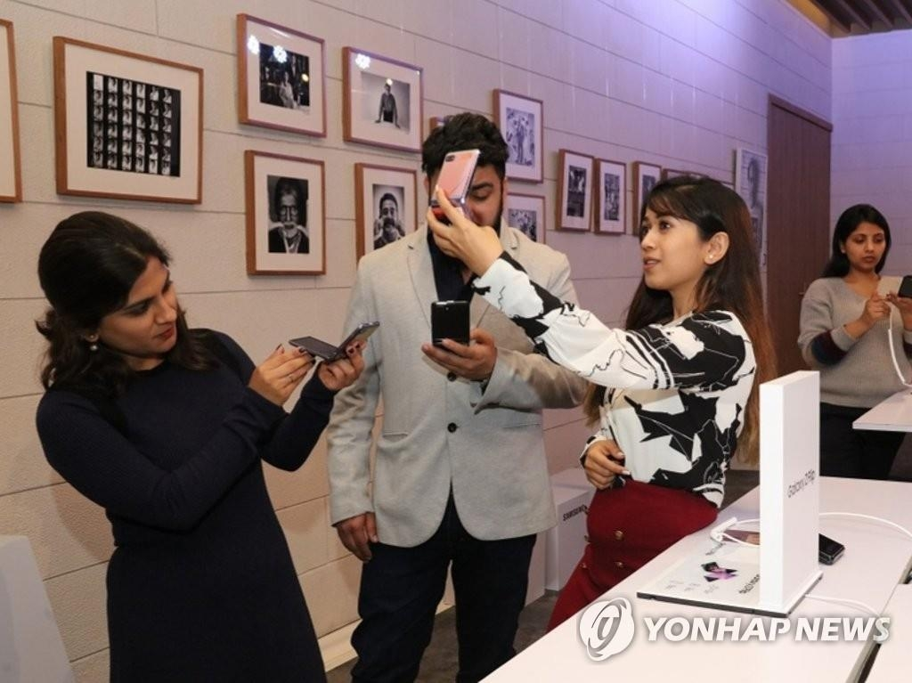 In this photo, provided by Samsung Electronics Co.'s Indian unit on Feb. 20, 2020, Indian consumers inspect the company's foldable smartphone, the Galaxy Z Flip, at an event in Gurugram, India. (PHOTO NOT FOR SALE) (Yonhap)