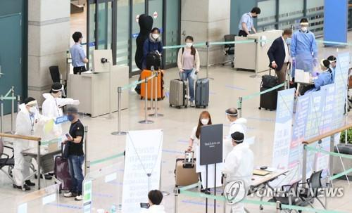 This photo taken July 28, 2020, shows health workers guiding arrivals at Incheon International Airport, west of Seoul. (Yonhap)