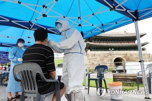 In this photo, taken on Aug. 10, 2020, health workers examine a citizen for a COVID-19 test at a makeshift clinic near Namdaemun Market in Seoul after eight merchants there tested positive for the virus. (Yonhap)