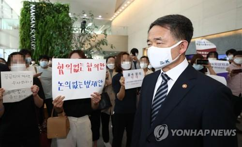 Health and Welfare Minister Park Neunghoo walks past trainee doctors who oppose the agreement reached between the government, parliament and the Korean Medical Association to end the two-week-long strike, in Seoul, on Sept. 4, 2020. (Yonhap)