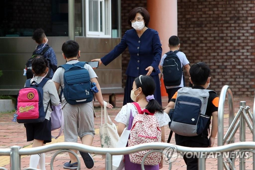 The undated file photo shows a teacher greeting children. (Yonhap)