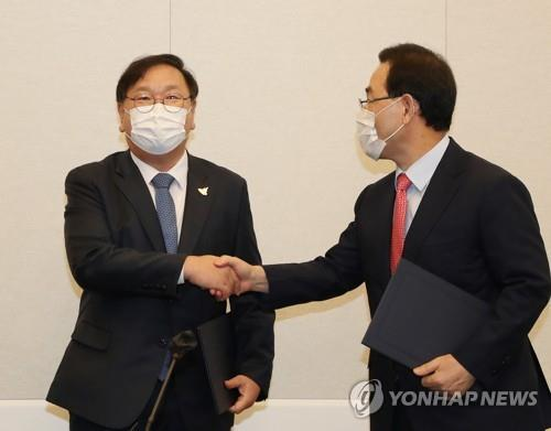 Democratic Party floor leader Rep. Kim Tae-nyeon (L) and People Power Party floor leader Rep. Joo Ho-young shake hands after reaching an agreement on the configuration of the fourth COVID-19 response extra budget, at the National Assembly in Seoul, on Sept. 22, 2020. (Yonhap)