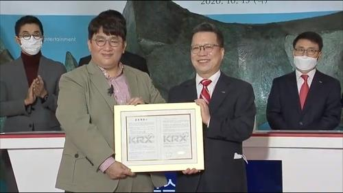 This photo, captured from Big Hit Entertainment's live video channel, shows Chairman and CEO Bang Si-hyuk (L) and Korea Exchange (KRX) Chairman and CEO Jung Ji-won posing for a photo at the K-pop entertainment giant's listing ceremony held at KRX's Seoul headquarters on Oct. 15, 2020. (Yonhap)