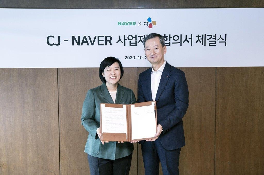 Han Seong-sook (L), CEO of Naver, and Choi Eun-seok, head of Management Strategy Office of CJ Corp., pose after signing a strategic partnership deal on Oct. 26, 2020, in this photo provided by Naver. (PHOTO NOT FOR SALE) (Yonhap)