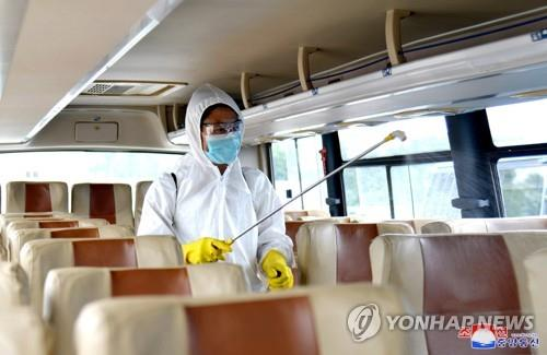An official disinfects a bus in Pyongyang amid the coronavirus pandemic, in this undated photo released by the North's official Korean Central News Agency on Sept. 4, 2020. (For Use Only in the Republic of Korea. No Redistribution) (Yonhap)