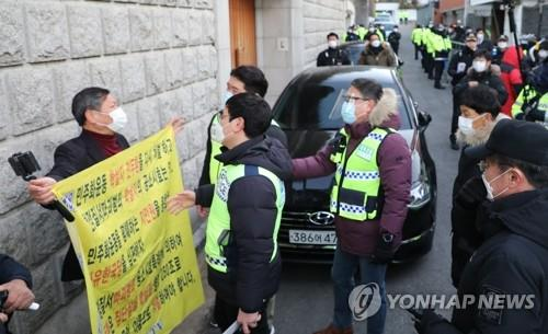 A civic activist demanding stern punishment for former President Chun Doo-hwan talks with police in front of Chun's residence in western Seoul on Nov. 30, 2020. (Yonhap)