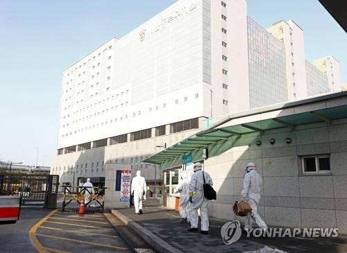 Medical workers walk in front of the entrance of Dongbu Detention Center in Seoul on Jan. 14, 2021. (Yonhap)