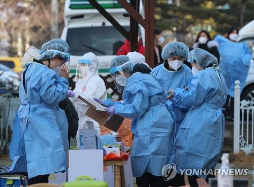 Medical workers prepare to set up a coronavirus testing site at a kindergarten in the southwestern provincial city of Gwangju, where a confirmed patient was reported to have visited, on Jan. 24, 2021, after a total of 15 new cases were traced to a church in the city. (Yonhap)