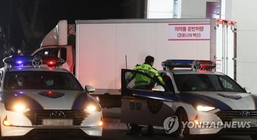 A truck carrying vials of AstraZeneca's vaccine departs from a cold chain logistics warehouse in Icheon, 80 km southeast of Seoul, under the strict guard of the Army and police on Feb. 25, 2021. (Yonhap)