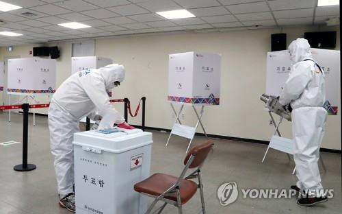 This file photo taken on April 1, 2021, shows quarantine officials disinfecting a polling station in Busan ahead of early voting for the city's April 7 mayoral by-election. (Yonhap)