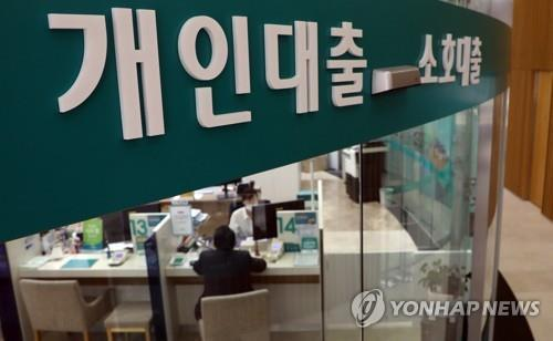 This file photo shows a bank official explaining a loan product to a visiting customer. (Yonhap)
