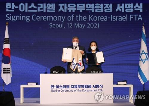 South Korean Trade Minister Yoo Myung-hee (R) and her Israeli counterpart Amir Peretz pose for a photo at a hotel in central Seoul on May 12, 2021, after signing a free trade agreement between the two countries. (Yonhap)