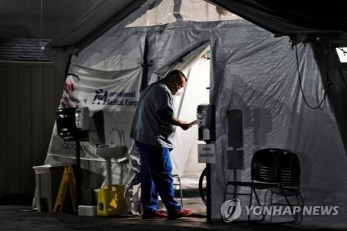 미 캘리포니아 헌팅턴파크 지역병원의 응급실 밖에 마련된 텐트에 있는 환자를 의료진이 점검하고 있다. [로이터=연합뉴스 자료사진]