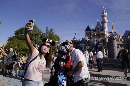 30일(현지시간) 1년여 만에 재개장한 미 캘리포니아 애너하임의 디즈니랜드에서 한 가족이 사진을 찍고 있다. [AP=연합뉴스]