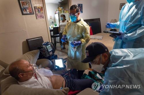 20일(현지시간) 미 텍사스주 휴스턴의 한 주택에서 텍사스 소방서 구급대원이 코로나19 환자의 상태를 점검하고 있다. [AFP=연합뉴스]