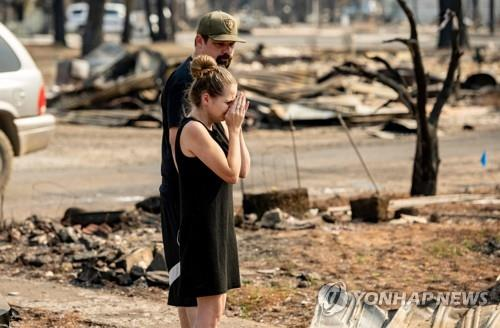 한 여성이 4일(현지시간) 미 캘리포니아 그린빌에서 발생한 딕시 화재로 잿더미가 된 어머니의 집을 보면서 울고 있다. 이 화재로 그린빌 마을 대부분이 파괴됐다. [AFP=연합뉴스]