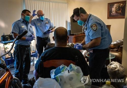 14일(현지시간) 미 텍사스주 휴스턴소방대 구급대원들이 코로나19에 감염된 40대 남성의 생체 신호를 검사하고 있다.