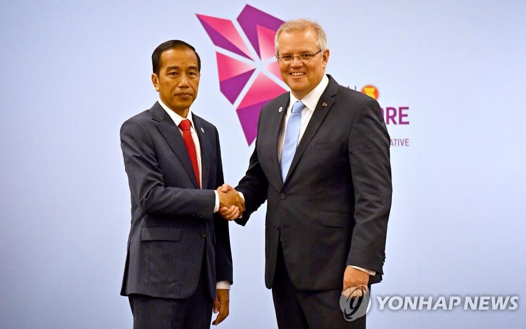 2018년 9월 14일 싱가포르에서 열린 2018 아세안 정상회의를 계기로 만난 조코 위도도 인도네시아 대통령(왼쪽)과 스콧 모리슨 호주 총리(오른쪽)가 악수를 나누고 있다. [EPA=연합뉴스자료사진]