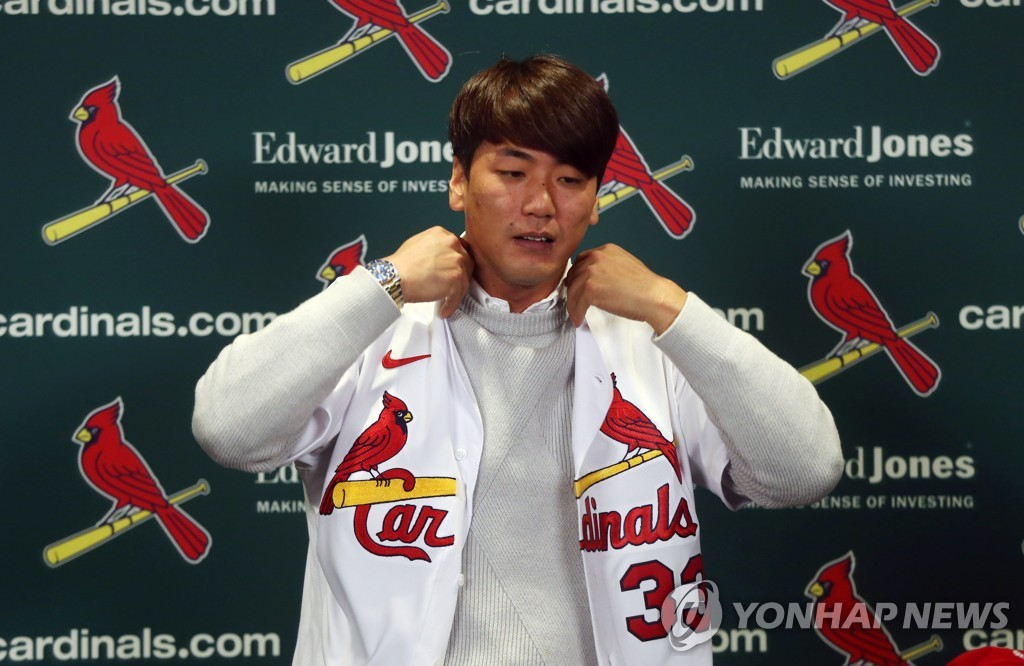 In this UPI file photo from Dec. 17, 2019, South Korean pitcher Kim Kwang-hyun puts on his new St. Louis Cardinals jersey during an introductory press conference at Busch Stadium in St. Louis. (Yonhap)