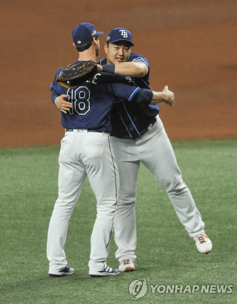 In this UPI photo, Choi Ji-man of the Tampa Bay Rays (R) embraces teammate Joey Wendle to celebrate their 8-2 victory over the Toronto Blue Jays to win their American League Wild Card Series at Tropicana Field in St. Petersburg, Florida, on Sept. 30, 2020. (Yonhap)