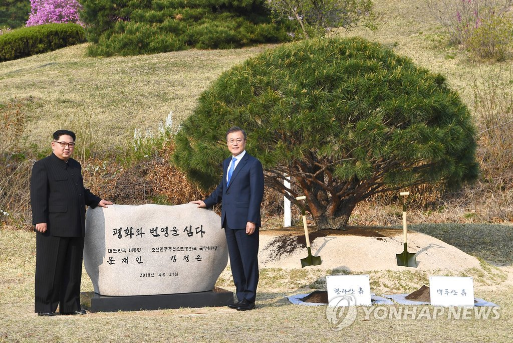"In this photo from April 27, 2018, provided by Yonhap News TV, South Korean President Moon Jae-in (R) and his North Korean counterpart, Kim Jong-un, pose beside a commemorative cornerstone after a tree-planting ceremony to mark their historic talks at the truce village of Panmunjom. The phrase on the stone reads, ""(We) Plant Peace and Prosperity. President Moon Jae-in of the Republic of Korea. Chairman of the State Affairs Commission Kim Jong-un of the Democratic People's Republic of Korea."" (PHOTO NOT FOR SALE) (Yonhap)"