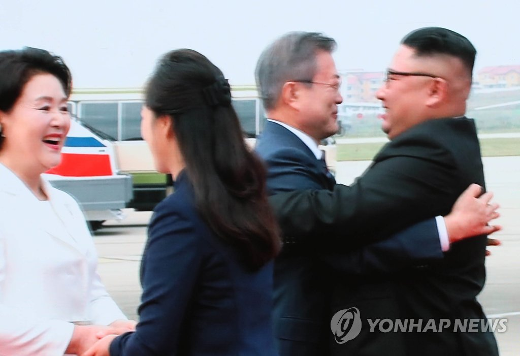 The captured image of a live broadcast from Pyongyang shows South Korean President Moon Jae-in (2nd from R) and North Korean leader Kim Jong-un embracing each other shortly after Moon's arrival in the North Korean capital on Sept. 18, 2018, for the leaders' third inter-Korean summit. (Yonhap)
