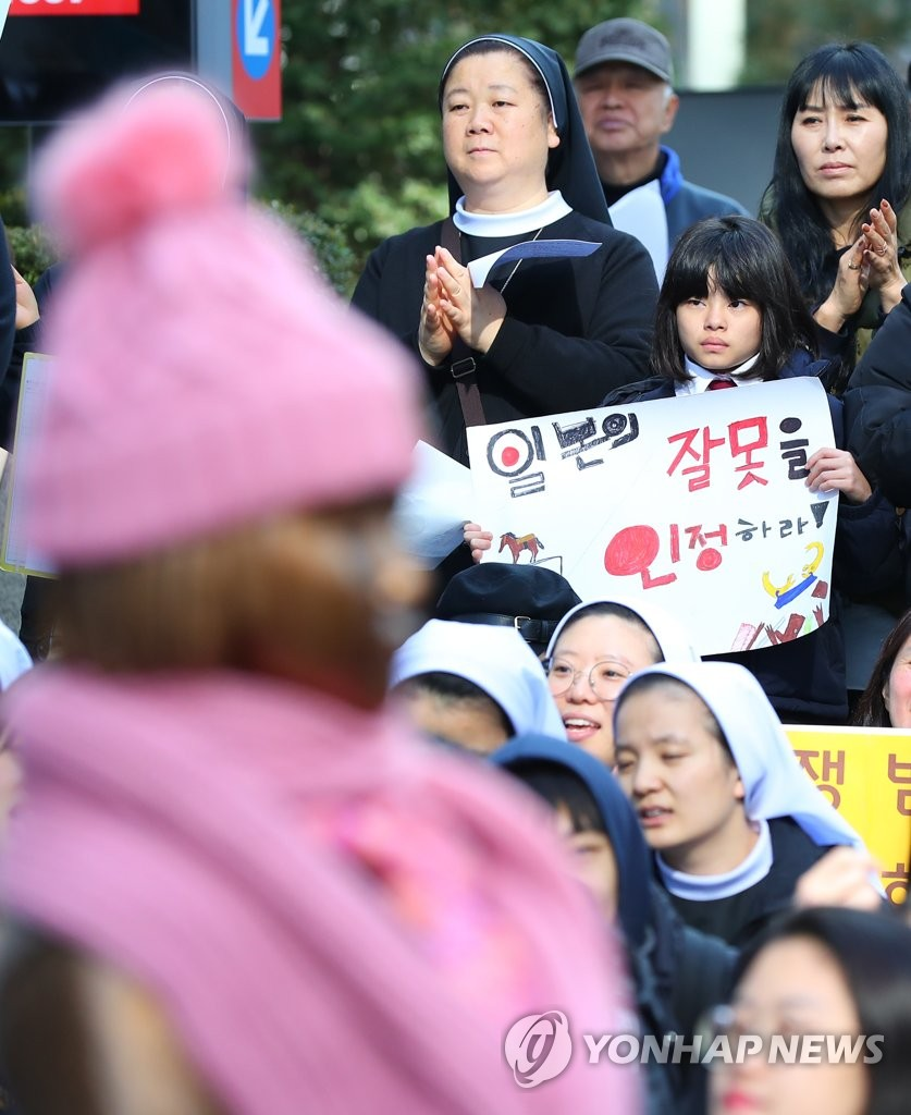 "South Koreans stage a weekly rally in Seoul against Japan's wartime sexual slavery in front of a ""girl statue for peace,"" which symbolizes victims, in this undated file photo. (Yonhap)"