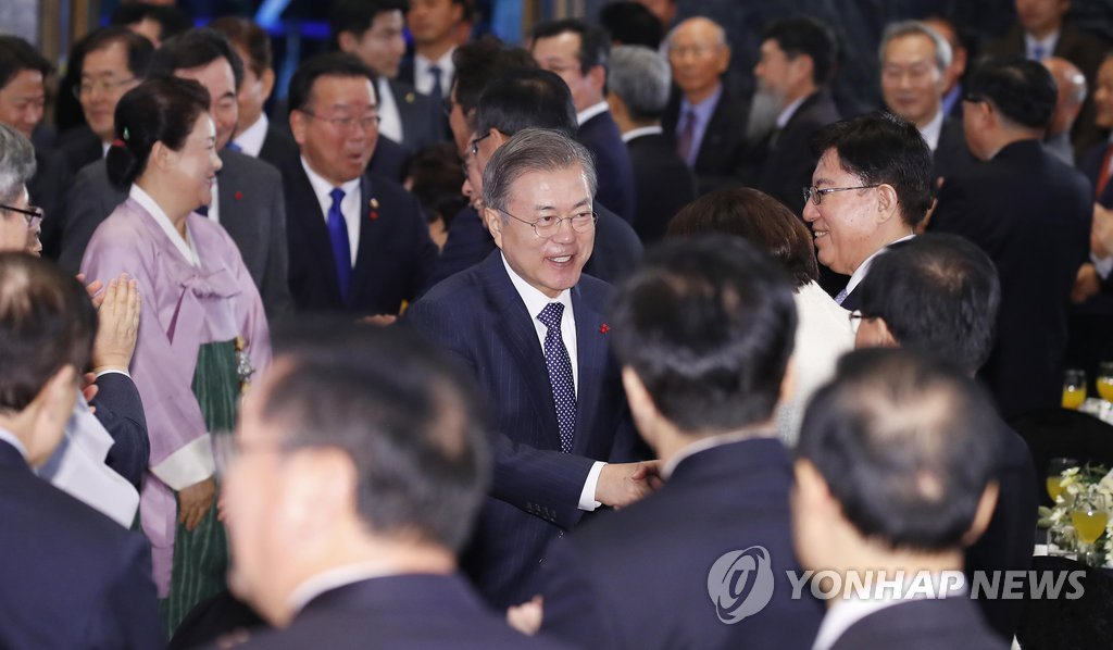 President Moon Jae-in shakes hands with other participants during a new year's meeting at the headquarters of the Korean Federation of SMEs in Seoul on Jan. 2, 2019. (Yonhap)